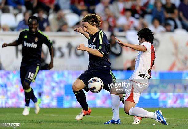 Luka Modric of Real Madrid CF tries to get past Jose Manuel Casado of Rayo Vallecano de Madrid during the La Liga match between Rayo Vallecano de...