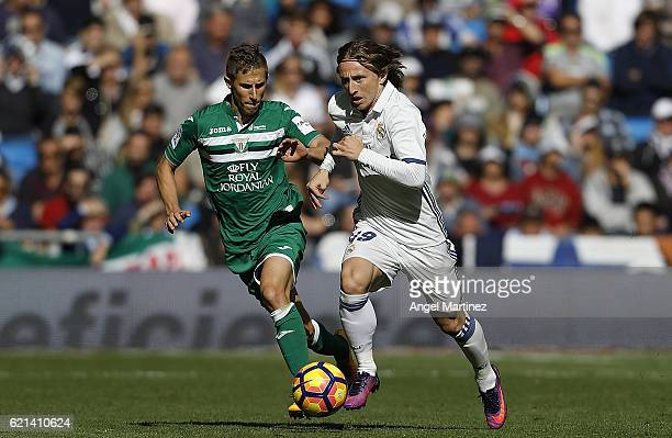 Luka Modric of Real Madrid competes for the ball with Alexander Szymanowski of Leganes during the La Liga match between Real Madrid CF and Leganes at...