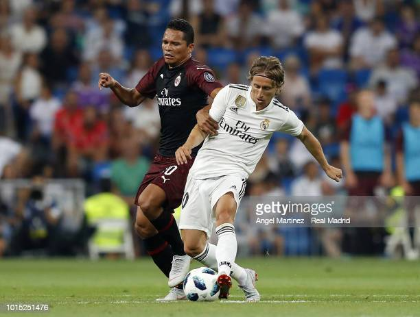 Luka Modric of Real Madrid competes for the ball with Carlos Bacca of AC Milan during the Trofeo Santiago Bernabeu match between Real Madrid and AC...