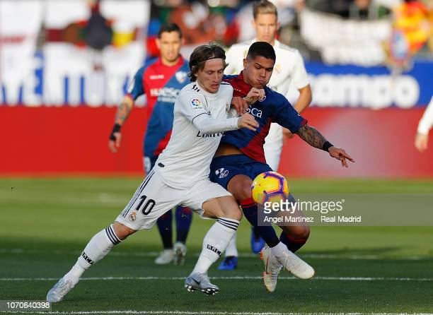 Luka Modric of Real Madrid competes for the ball with Cucho of SD Huesca during the La Liga match between SD Huesca and Real Madrid CF at Estadio El...