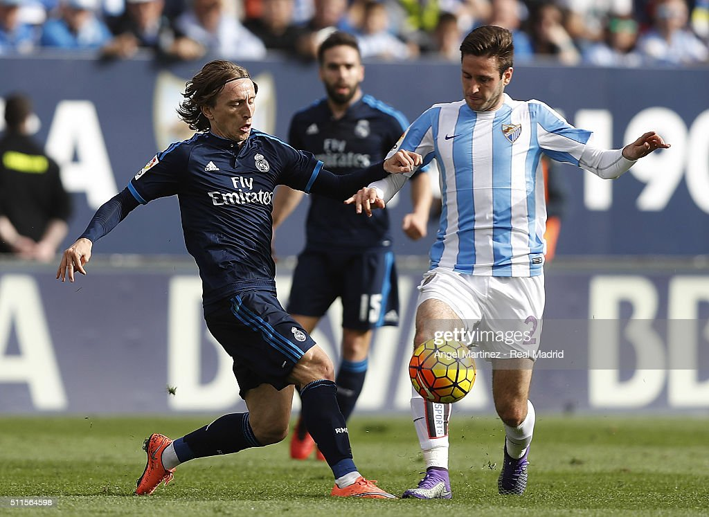 Luka Modric of Real Madrid competes for the ball with Duje Cop of Malaga CF during the La Liga match between Malaga CF and Real Madrid CF at La Rosaleda Stadium on February 21, 2016 in Malaga, Spain.