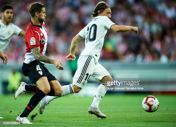 Luka Modric of Real Madrid competes for the ball with Inigo Martinez of Athletic Club during the La Liga match between Athletic Club Bilbao and Real...