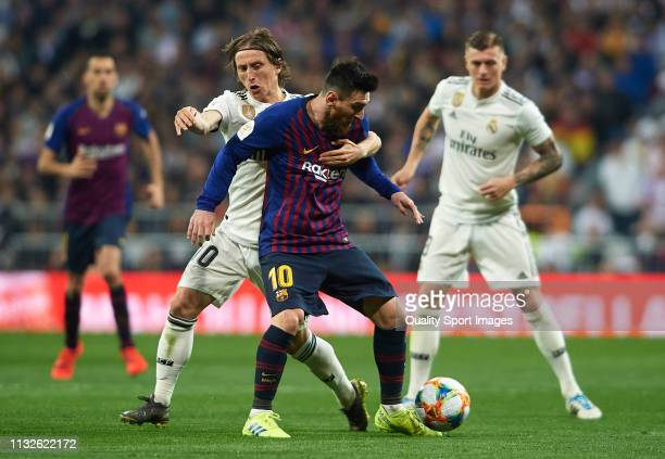 Luka Modric of Real Madrid competes for the ball with Lionel Messi of Barcelona during the Copa del Rey Semi Final second leg match between Real...