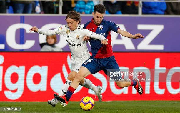 Luka Modric of Real Madrid competes for the ball with Moi Gomez of SD Huesca during the La Liga match between SD Huesca and Real Madrid CF at Estadio...