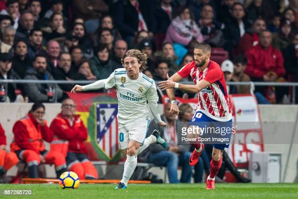 Luka Modric of Real Madrid competes for the ball with Yannick Ferreira Carrasco of Atletico de Madrid during the La Liga 201718 match between...