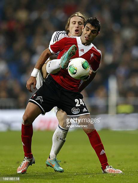 Luka Modric of Real Madrid duels for the ball with Augusto Fernandez of Celta de Vigo during the round of 16 Copa del Rey second leg match between...