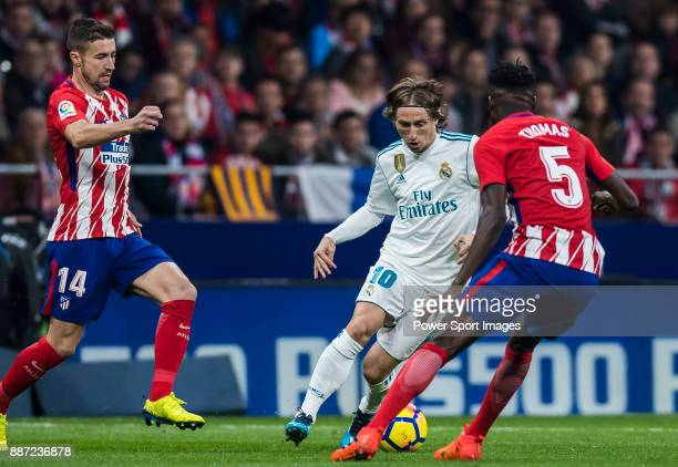 Luka Modric of Real Madrid fights for the ball with Thomas Teye Partey of Atletico de Madrid during the La Liga 201718 match between Atletico de...