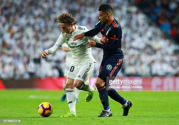 Luka Modric of Real Madrid holds off Francis Coquelin of Valencia during the La Liga match between Real Madrid CF and Valencia CF at Estadio Santiago...