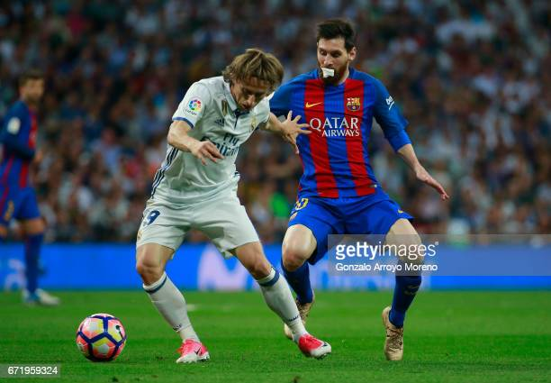 Luka Modric of Real Madrid holds off Lionel Messi of Barcelona during the La Liga match between Real Madrid CF and FC Barcelona at Estadio Bernabeu...