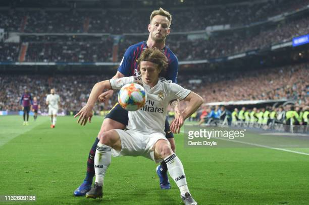 Luka Modric of Real Madrid is challenged by Ivan Rakitic of FC Barcelona during the Copa del Rey Semi Final second leg match between Real Madrid and...