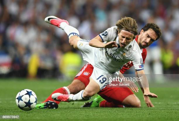 Luka Modric of Real Madrid is challenged by Mats Hummels of Bayern Muenchen during the UEFA Champions League Quarter Final second leg match between...