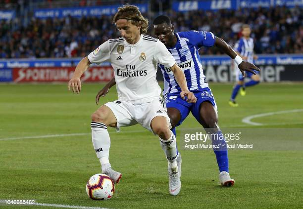 Luka Modric of Real Madrid is challenged by Wakaso Mubarak of Deportivo Alaves during the La Liga match between Deportivo Alaves and Real Madrid at...