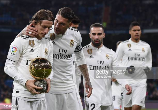 Luka Modric of Real Madrid is congratulated by team captain Sergio Ramos while presenting his Balon d'Or Trophy to the crown prior to the La Liga...