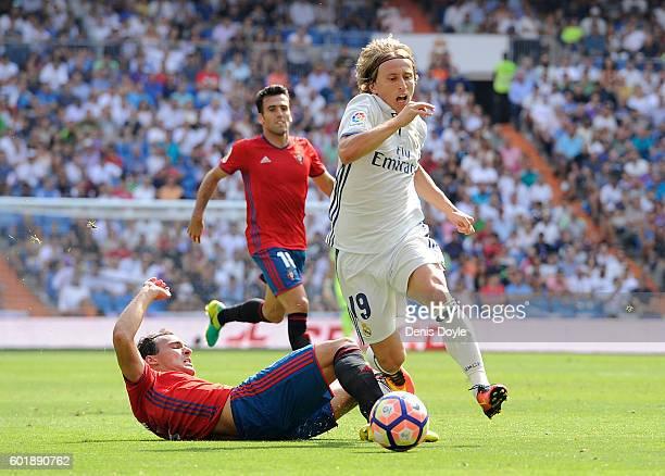 Luka Modric of Real Madrid is fouled by Unai Garcia of CA Osasuna during the La Liga match between Real Madrid CF and CA Osasuna at Estadio Santiago...
