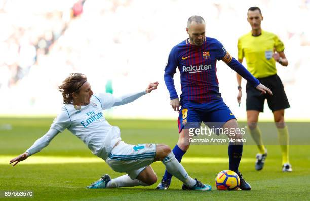 Luka Modric of Real Madrid tackles Andres Iniesta of Barcelona during the La Liga match between Real Madrid and Barcelona at Estadio Santiago...