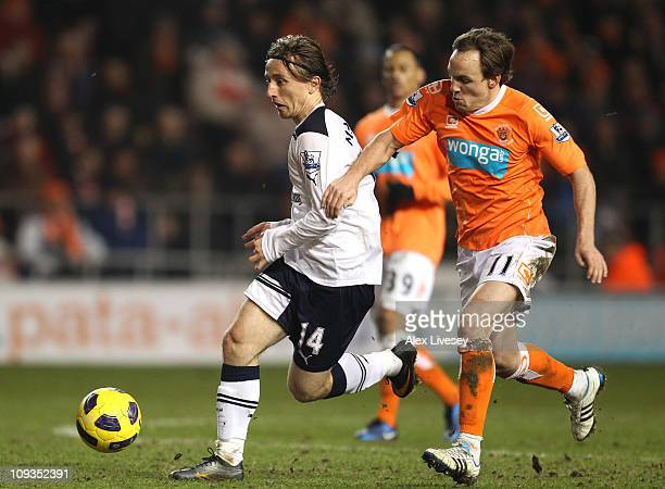 Luka Modric of Tottenham Hotspur holds off a challenge from David Vaughan of Blackpool during the Barclays Premier League match between Blackpool and...