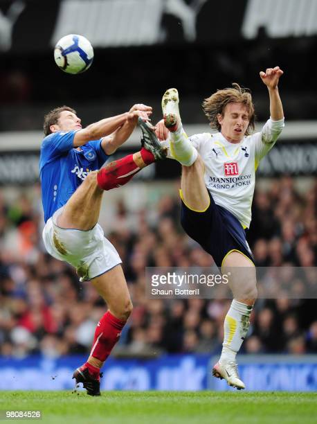Luka Modric of Tottenham Hotspur is challenged by Michael Brown of Portsmouth during the Barclays Premier League match between Tottenham Hotspur and...