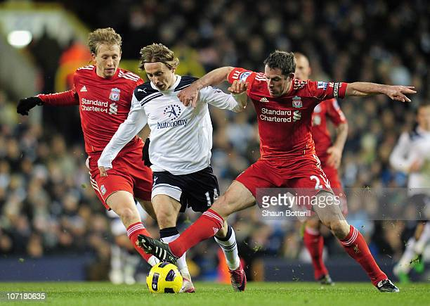 Luka Modric of Tottenham Hotspur is tackled by Jamie Carragher of Liverpool during the Barclays Premier League match between Tottenham Hotspur and...