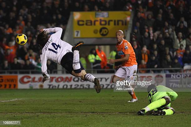 Luka Modric of Tottenham Hotspur trips over Richard Kingson of Blackpool as he shoots towards goal during the Barclays Premier League match between...