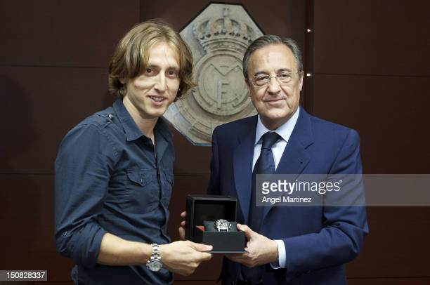 Luka Modric receives a gift from Real Madrid president Florentino Perez before his official presentation at Santiago Bernabeu stadium on August 27...