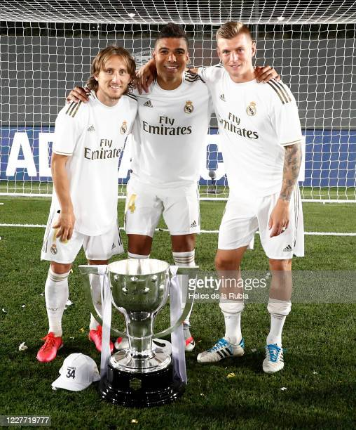 Luka Modric, Toni Kroos and Casemiro player of Real Madrid poses with the La Liga trophy after Madrid secure the La Liga title during the Liga match...