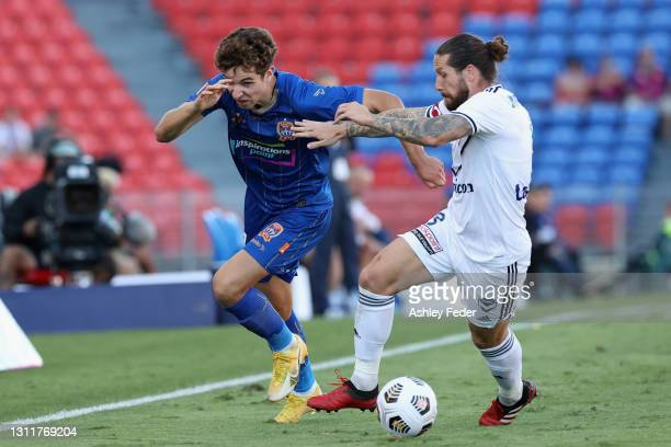 Luka Prso of the Jets contests the ball against Jacob Butterfield of Melbourne Victory during the A-League match between the Newcastle Jets and the...