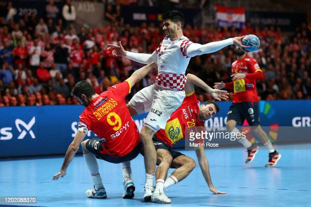 Luka Stepancic of Croatia is challenged by Raul Entrerrios Rodriguez and Aitor Arino Bengoechea of Spain during the Men's EHF EURO 2020 final match...