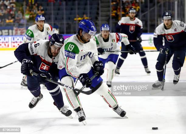 Lukas Cingel of Slovakia challenges Rapahel Andergassen of Italy for the puck during the 2017 IIHF Ice Hockey World Championship game between...