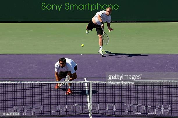 Lukas Dlouhy of Czech Republic serves to Marcel Granollers and Marc Lopez of Spain while playing with Marin Cilic of Croatia during the Sony Open at...