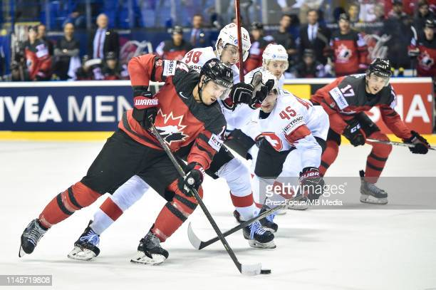 Lukas Frick of Switzerland tackles Adam Henrique of Canada during the 2019 IIHF Ice Hockey World Championship Slovakia quarter final game between...