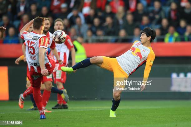 Lukas Graf of Grazer AK competes for the ball with Takumi Minamino of RB Salzburg during the UNIQA OeFB Cup Semifinal match between Grazer AK and Red...