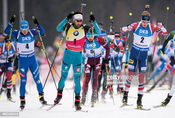 Lukas Hofer of Italy Martin Fourcade of France and Johannes Thingnes Boe of Norway in action during the men's mass start event of the Biathlon World...