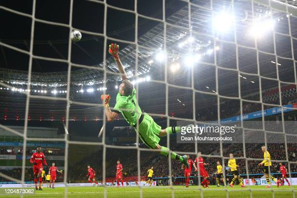 Lukas Hradecky of Bayer 04 Leverkusen dives for the ball as Emre Can of Borussia Dortmund scores his team's second goal during the Bundesliga match...