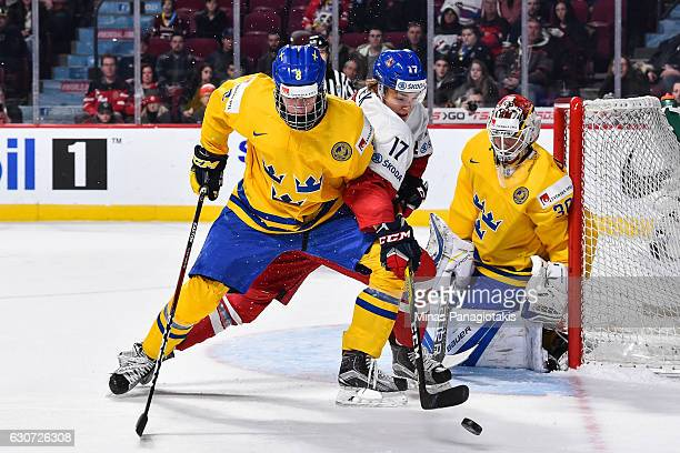 Lukas Jasek of Team Czech Republic and Rasmus Dahlin of Team Sweden battle for the puck while goaltender Filip Gustavsson defends his net during the...
