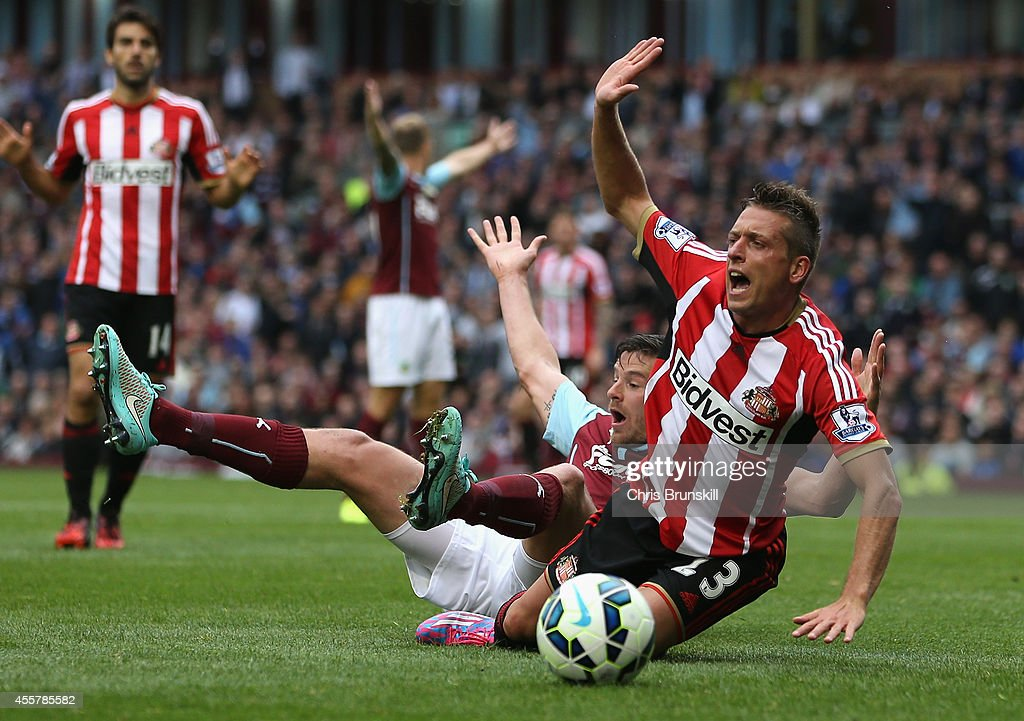Lukas Jutkiewicz of Burnley tangles in the penalty box with Emanuele Giaccherini of Sunderland during the Barclays Premier League match between Burnley and Sunderland at Turf Moor on September 20, 2014 in Burnley, England.