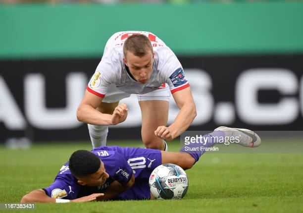 Lukas Klostermann of Leipzig is challenged by Anas Ouahim of Osnabrueck during the DFB Cup first round match between VfL Osnabrueck and RB Leipzig at...