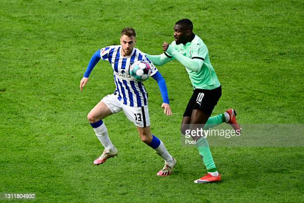 Lukas Kluenter of Hertha Berlin battles for possession with Marcus Thuram of Borussia Moenchengladbach during the Bundesliga match between Hertha BSC...