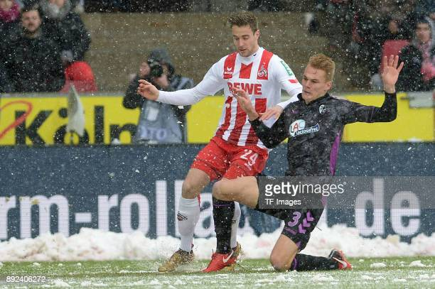 Lukas Kluenter of Koeln and Philipp Lienhart of Freiburg battle for the ball during the Bundesliga match between 1 FC Koeln and SportClub Freiburg at...