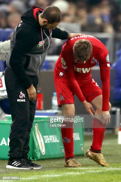 Lukas Kluenter of Koeln shows his injuring to head coach Stefan Ruthenbeck during the DFB Cup match between FC Schalke 04 and 1FC Koeln at...