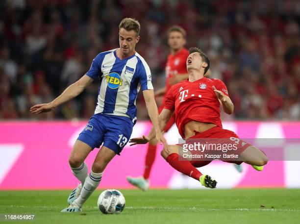 Lukas Klunter of Hertha BSC tackles Robert Lewandowski of FC Bayern Munich during the Bundesliga match between FC Bayern Muenchen and Hertha BSC at...
