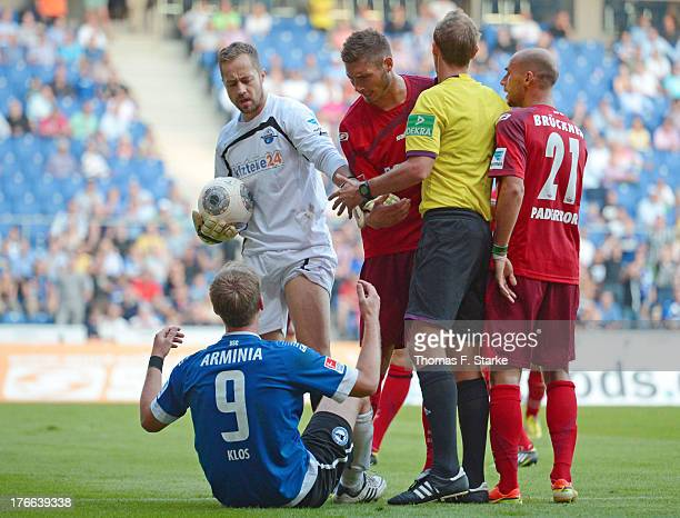 Lukas Kruse Christian Strohdiek and Daniel Brueckner of Paderborn argue with Fabian Klos of Bielefeld while referee Sascha Stegemann arbitrates...