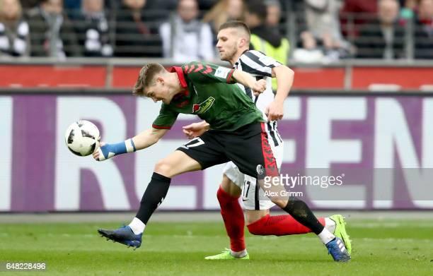 Lukas Kuebler of Freiburg is challenged by Ante Rebic of Frankfurt during the Bundesliga match between Eintracht Frankfurt and SC Freiburg at...