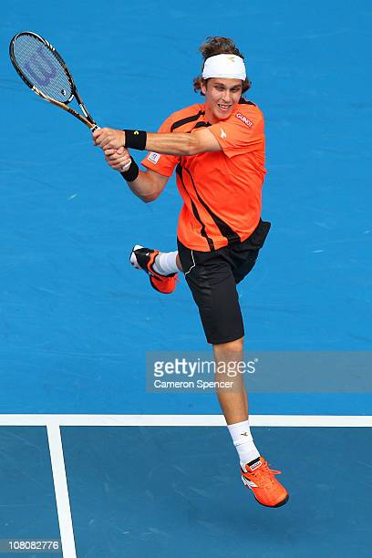 Lukas Lacko of Slovakia plays a backhand in his first round match against Roger Federer of Switzerland during day one of the 2011 Australian Open at...