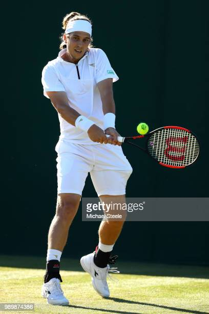 Lukas Lacko of Slovakia returns against Benjamin Bonzi of France during their Men's Singles first round match on day one of the Wimbledon Lawn Tennis...