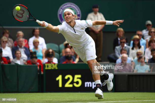 Lukas Lacko of Slovakia returns against Roger Federer of Switzerland during their Men's Singles second round match on day three of the Wimbledon Lawn...