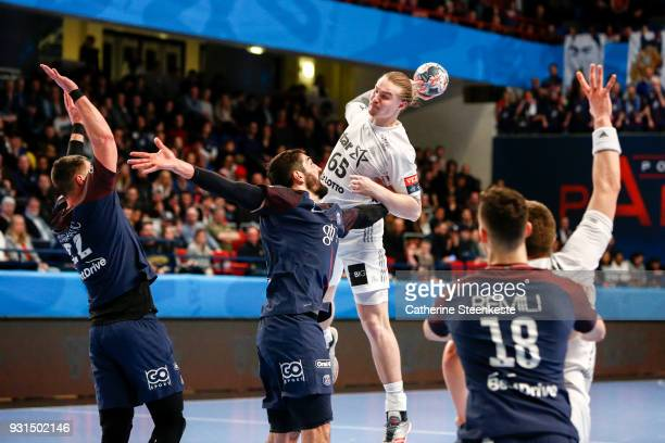 Lukas Nilsson of THW Kiel is shooting the ball against Nikola Karabatic and Luka Karabatic of Paris Saint Germain during the Champions League match...