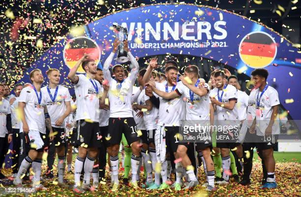 Lukas Nmecha of Germany lifts the UEFA European Under-21 Championship trophy in celebration with team mates after winning the 2021 UEFA European...
