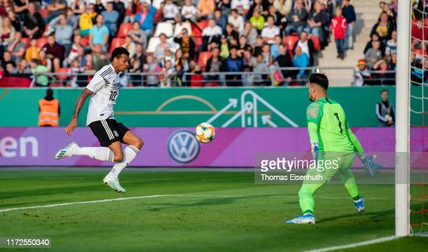 Lukas Nmecha of Germany scores the opening goal past goalkeeper Marios Siampanis of Greece during the U21 international friendly match between...
