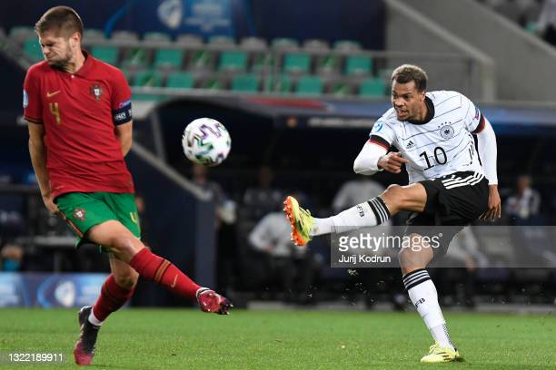 Lukas Nmecha of Germany shoots whilst under pressure from Diogo Queiros of Portugal during the 2021 UEFA European Under-21 Championship Final match...