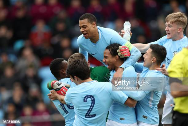 Lukas Nmecha of Manchester City leads the celebrations after Daniel Grimshaw saves a penalty to win the UEFA Youth League QuarterFinal at Manchester...